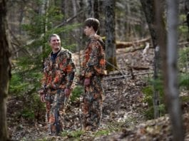 Barrie North, left, and Peter North, right, a father-son duo from Strafford, Vt., talk in the woods behind their home on Thursday while sporting their new invention.