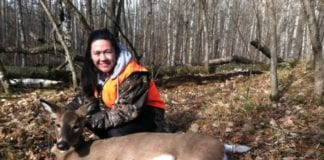 Young female hunter poses with harvested White-tailed deer taken during the Minnesota firearms deer season.