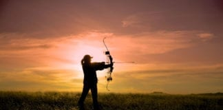 a bowhunter silhouetted against a brilliant sunset