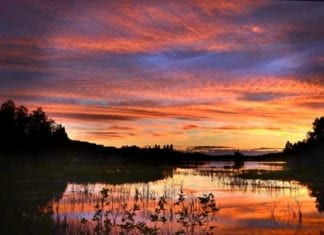 The Texas sun setting over one of the various fishing ponds at the Lazy J Ranch - Hunting Magazine