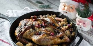 holiday roast baked duck on roasted vegetables in cast iron pan with cranberries | Hunting Magazine